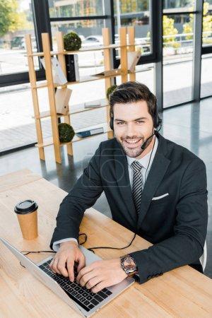 lächelnder Callcenter-Betreiber mit Headset am Arbeitsplatz mit Laptop im Büro