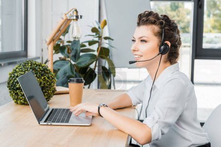 side view of smiling female call center operator with headset at workplace in office