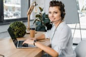 young smiling female call center operator with headset at workplace in office