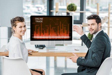 Photo pour Collègues de travail souriant au milieu de travail avec l'écran de l'ordinateur avec le commerce en ligne, inscription au bureau - image libre de droit