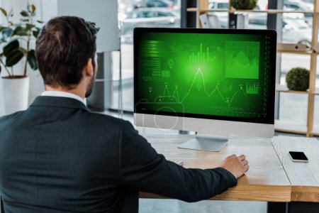 Photo for Back view of businessman at workplace with computer screen with diagram in office - Royalty Free Image