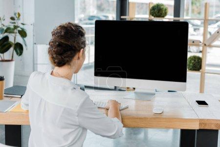 Photo pour Vue arrière du femme d'affaires travaillant sur ordinateur avec un écran blanc au bureau - image libre de droit