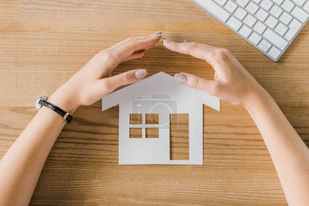 Partial view of businesswoman covering house paper model on wooden tabletop with hands, insurance concept