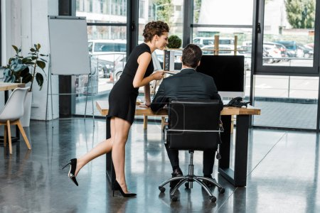 young businesswoman holding colleagues tie while flirting at workplace in office