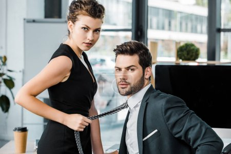 side view of businesswoman holding colleagues tie while flirting at workplace in office