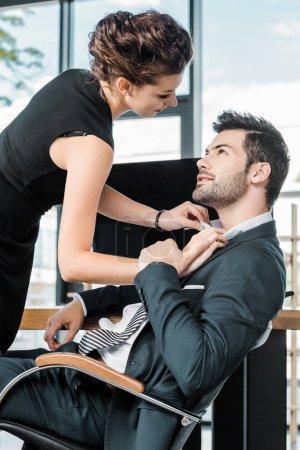 vue latérale de la chemise de collègues unbuttoning jeune femme d'affaires au lieu de travail au bureau