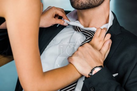 partial view of businesswoman unbuttoning colleagues shirt in office