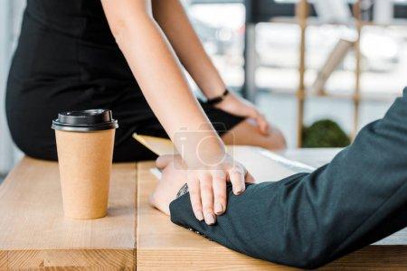 Photo pour Plan recadré de femme d'affaires flirtant avec un collègue au travail dans le bureau - image libre de droit