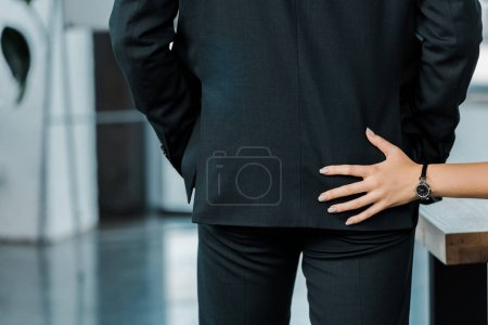 cropped shot of businesswoman flirting with colleague in office