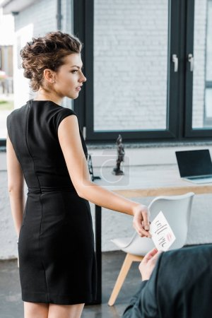 partial view of young businesswoman giving call me note to colleague in office