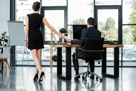 rear view of businesswoman giving call me note to colleague at workplace in office