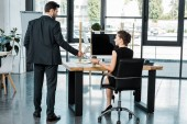 back view of businessman giving call me note to businesswoman at workplace in office