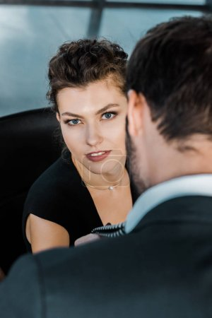 partial view of businesswoman holding businessmans tie while flirting