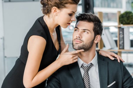 young seductive businesswoman flirting with colleague in office