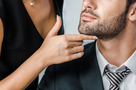 partial view of businesswoman flirting with businessman in suit