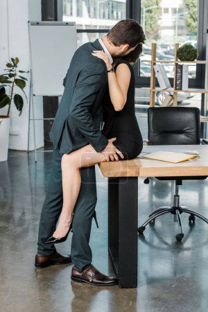 side view of sexy couple of business colleagues at workplace in office