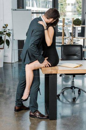 Photo pour Vue latérale de couple sexy de collègues d'affaires sur le lieu de travail au bureau - image libre de droit