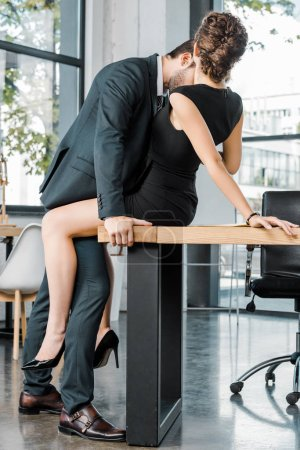 Photo for Side view of sexy couple of business colleagues at workplace in office - Royalty Free Image