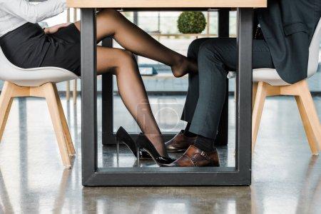 Photo pour Coup de projectile recadré de femme d'affaires flirtant avec l'homme d'affaires pendant le travail au bureau - image libre de droit
