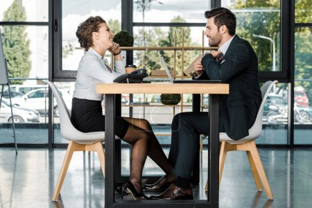 side view of young businesswoman flirting with businessman during work in office