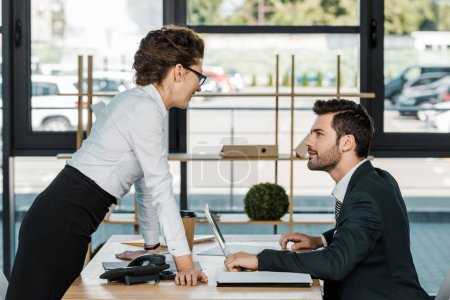Photo for Side view of smiling businesswoman looking at colleague at workplace with laptop in office - Royalty Free Image