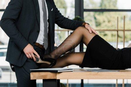 Photo pour Vue partielle d'un homme d'affaires passionné et d'une femme d'affaires sur le lieu de travail au bureau - image libre de droit