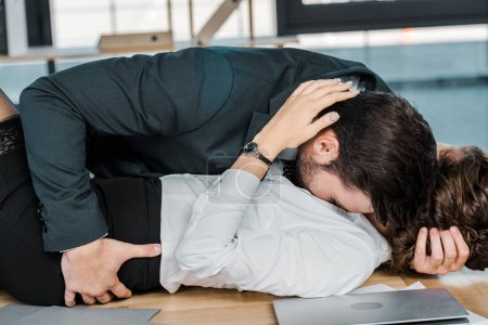 passionate businessman and businesswoman lying on table in office