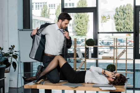 passionate businessman and businesswoman on table in office