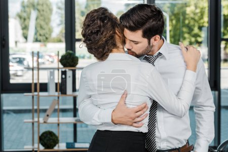 passionate business colleagues in formal wear hugging in office