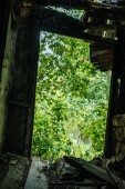 low angle view of abandoned building with broken roof and green trees in hole