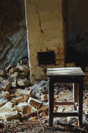 abandoned building with broken brick wall and wooden dirty chair