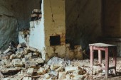 abandoned building with broken brick wall and wooden chair with dust