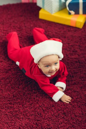 adorable little baby in santa suit lying on red carpet