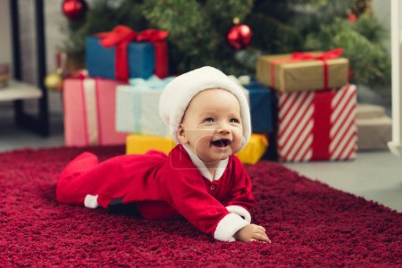 Photo for Laughing little baby in santa hat lying on floor in front of christmas tree and gifts - Royalty Free Image