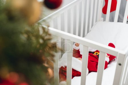 adorable little baby in santa suit lying in crib with christmas tree on foreground