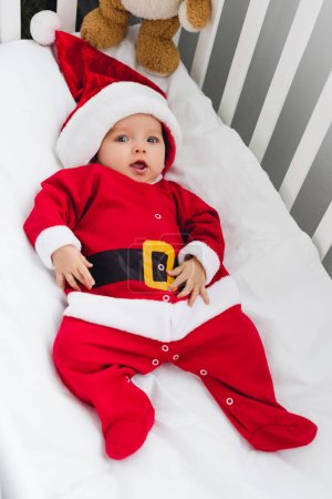 high angle view of adorable little baby in santa suit lying in crib with teddy bear and looking at camera