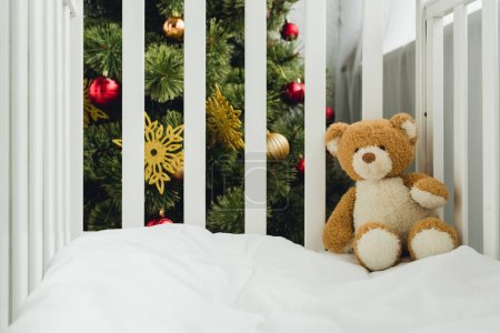 teddy bear in infant bed in front of christmas tree