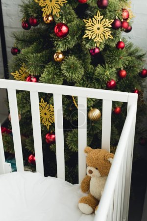 high angle view of teddy bear in infant bed in front of christmas tree