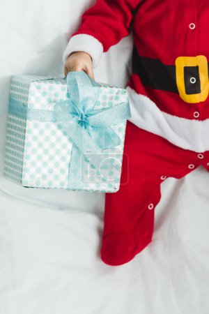 cropped shot of little baby in santa suit lying in crib with christmas gift