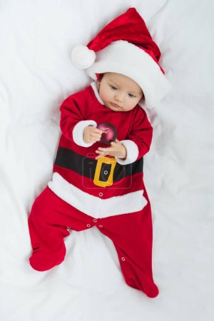 top view of beautiful little baby in santa suit holding christmas bauble while lying in crib