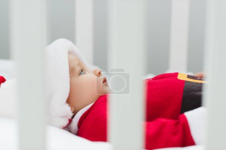 close-up shot of cute little baby in santa suit lying in crib