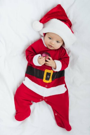 top view of adorable little baby in santa suit holding christmas bauble while lying in crib