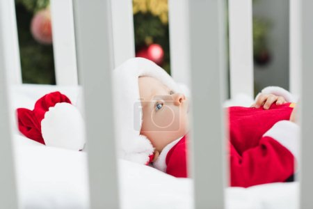 close-up shot of adorable little baby in santa suit lying in crib