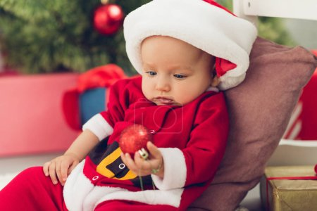 adorable little baby in santa suit holding christmas bauble