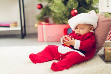 adorable little baby in santa suit sitting on floor with blurred christmas tree on background
