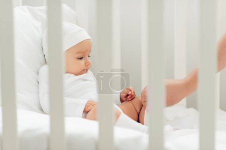 adorable little baby in white hat sitting in crib