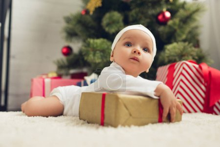 cute little baby lying on floor with christmas gifts