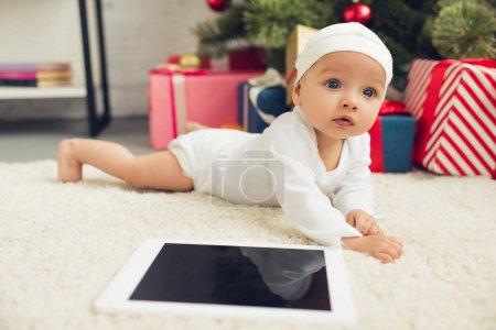 gros plan de beau petit bébé avec tablette gisant sur le sol avec les cadeaux de Noël et arbre floue sur fond