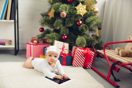 adorable little baby with tablet lying on floor near christmas gifts and tree and looking at camera