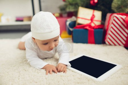 adorable little baby with tablet lying on floor with christmas gifts blurred on background